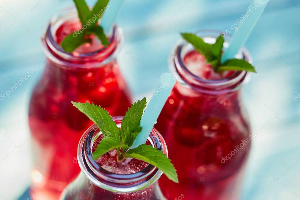 Three glasses of lemonade with raspberries