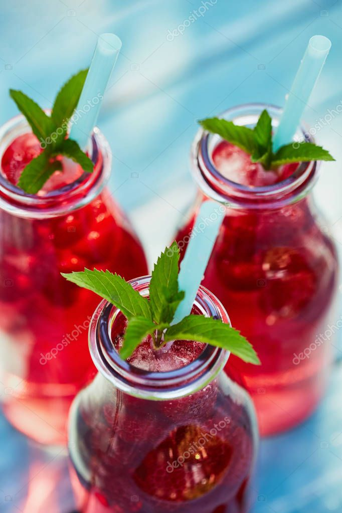Three glasses of lemonade with raspberries, top view
