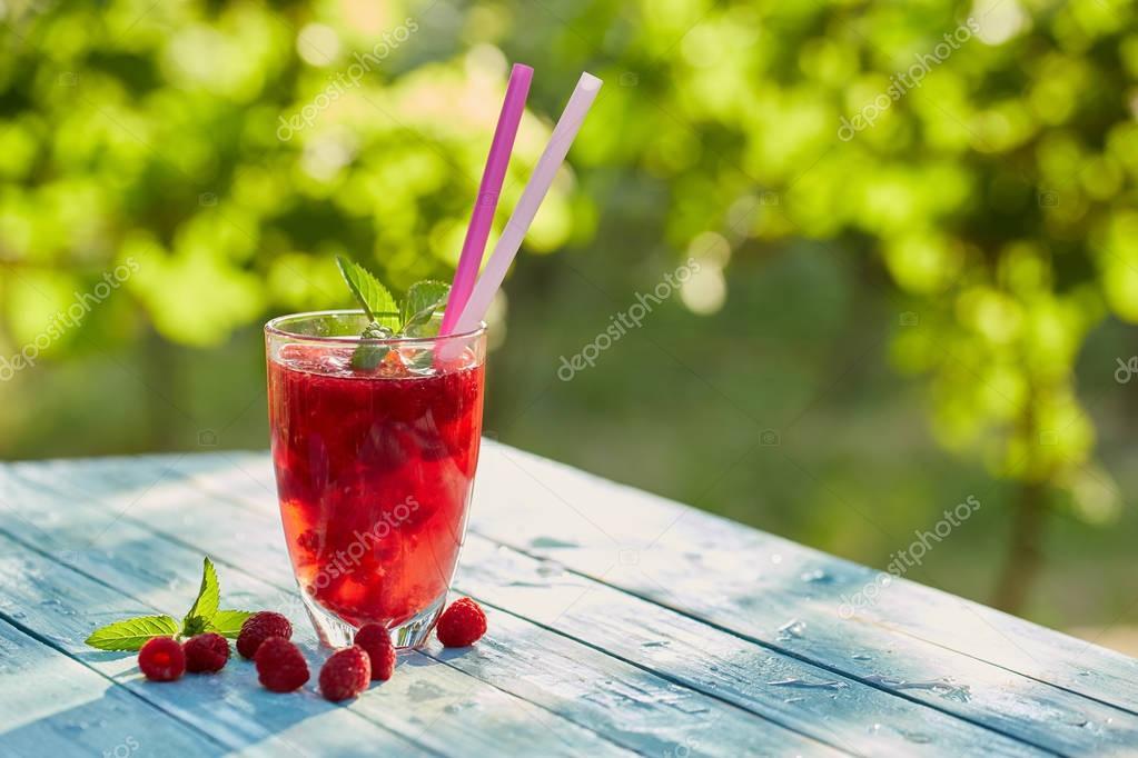 Glass of lemonade with raspberries