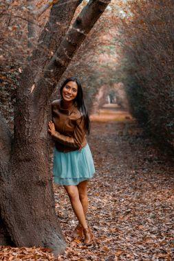 Diana, una chica junto a un arbol de los miles dentro de los senderos en los viveros de Coyoacan, Ciudad de Mexico. Un bosque dentro de la ciudad.