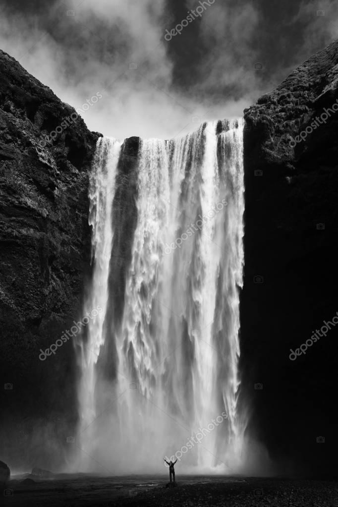 Silhouette of human near amazing waterfall