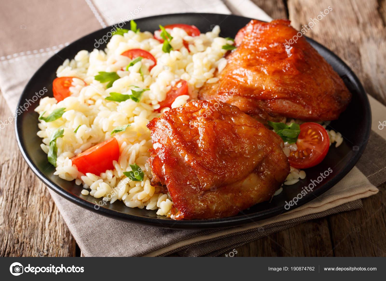 Portion gebratene Hähnchenschenkel mit Garnierung von Reis mit ...