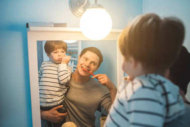 Young father with his son brushing teeth