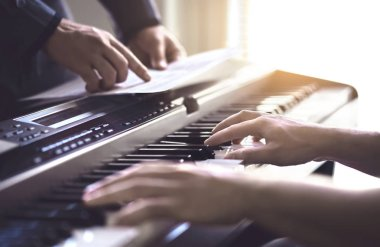 Piano teacher and student practising. Music lesson and course in school. Man learn playing with tutor in class. Mentor teaching pianist. Band practise. Two guys training. Hobby and education concept.