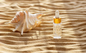 Photo Moisturizing face serum in a clear bottle. Marine background. Close up. Beauty and wellness concept.