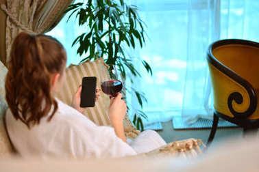 Woman in a white bathrobe with smartphone and wine is relaxing on a hotel bed.