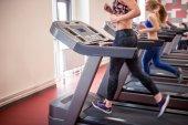 passen Sie Frauen laufen auf Laufbändern im modernen Fitnessraum