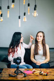 Beauty fashion blogger recording video with her friend