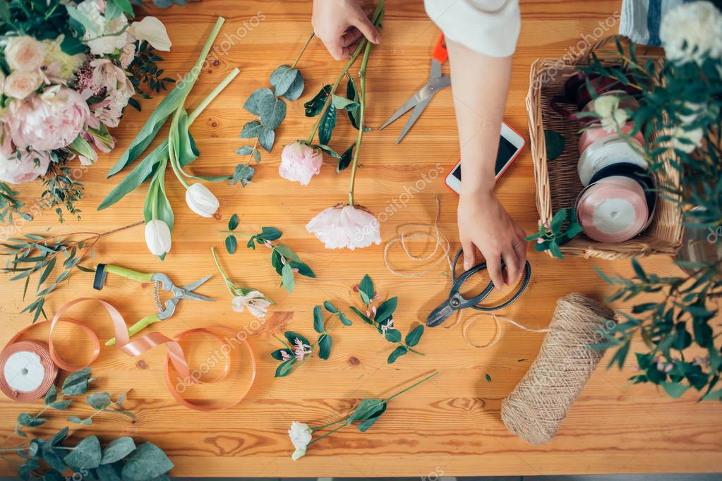 hands of florist against desktop with working tools and ribbons on wood table