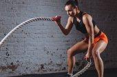 Fotografie Frau mit Schlacht Seil in cross-Fit Fitness-Studio trainieren