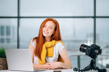 Young female blogger with laptop and book on camera screen looking at camera