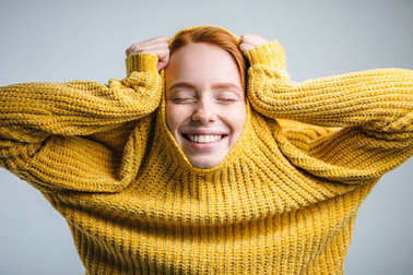 Fashion young woman pulling yellow sweater and having fun over white background