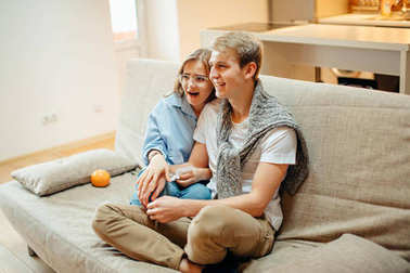 couple watching TV at home, having rest after hard week, copy space