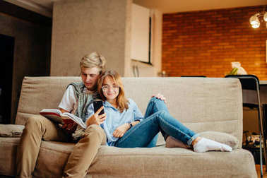 couple sitting on sofa, leisure together, man reading book, woman using phone