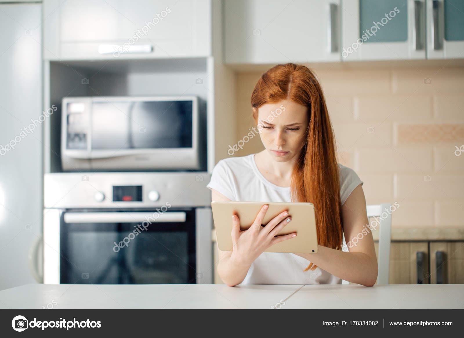 Unternehmerin Denken während der Arbeit am Tisch in ihrer Küche zu ...