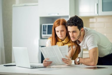Worried couple paying their bills online with laptop at home in living room