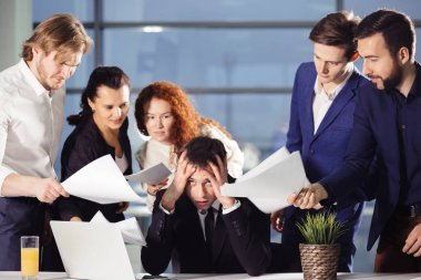 Stressed Business Man In Office surrounded by colleagues with documents in hands