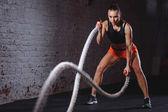 Fotografie Schlacht Seile Sitzung. Attraktive junge passen und durchtrainierten Sportlerin training im Fitness-Studio