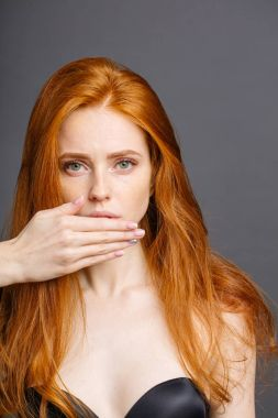 redhead woman covering mouth with hand and looking at camera on grey background