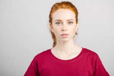 beautiful young redhead girl with clean fresh face and neutral emotions close up