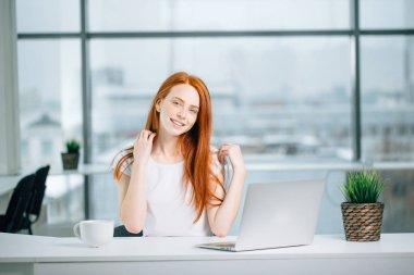 beautiful redhead girl works at laptop and looking at camera