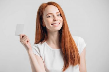 redhead girl holding credit card and smiling on white background.