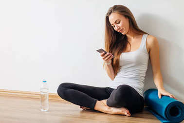 woman doing yoga and using cell phone sitting on the floor