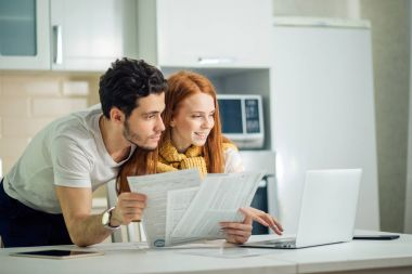 Happy couple at home paying bills with laptop