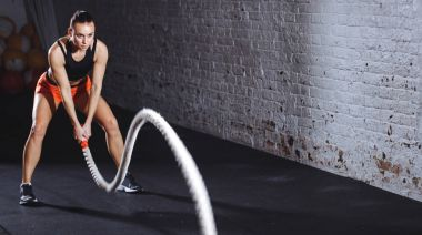 Woman doing cross fit exercise with one battle rope