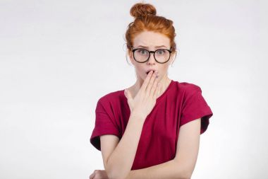 Shocked woman in glasses looking at camera with open mouth and touching head