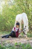 schöne Frau auf dem Boden sitzend mit braunem Pferd in ihrer Nähe.