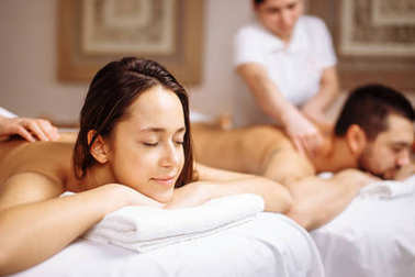 Happy couple getting massage at spa