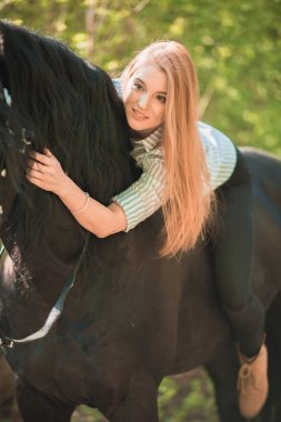 Young rider girl with long hair lying on horse neck