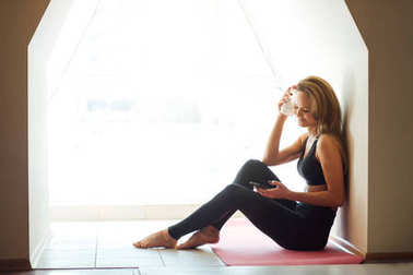 girl holding smart phone, resting on the white wooden floor after exercises