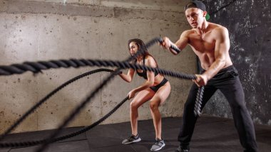 Woman and man couple training together doing battling rope workout