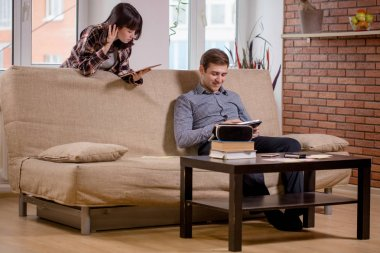 students learning for examinations together with eBook in home interior