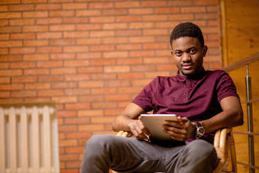 African man using tablet for video conversation while relaxing on armchair