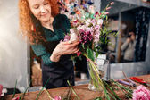 Photo female putting winsome flowers in vase in florists shop
