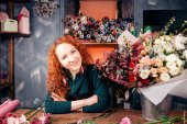 Photo florist-designer with red hair and green eyes working at florists shop