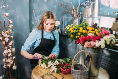 blond female cutting bad flowers at flower market