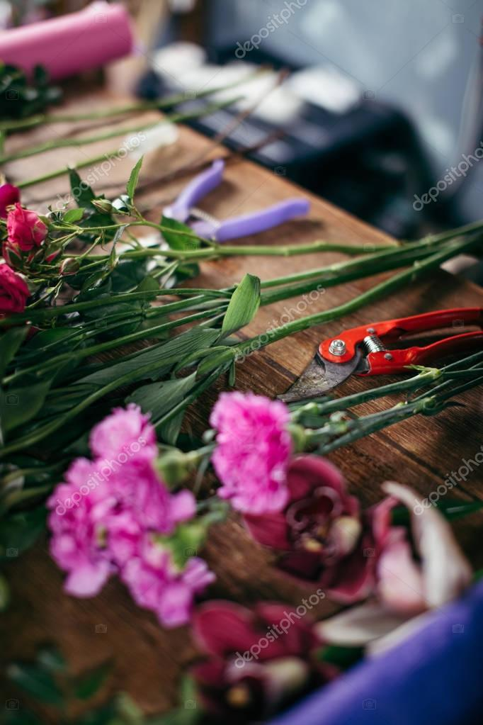 table with flowers and garden tools at shop