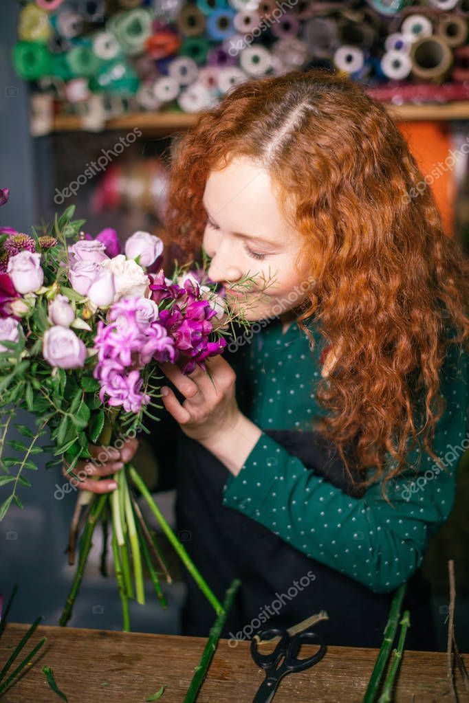 attractive Caucasion female holding bouquet of flowers and smelling them
