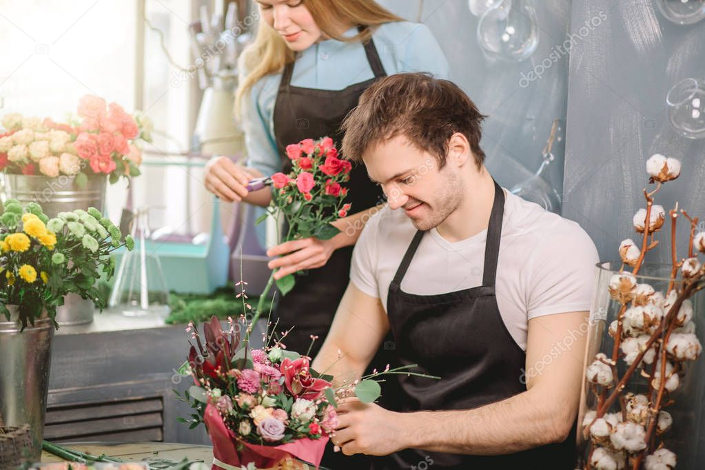 couple making order of customers at florists