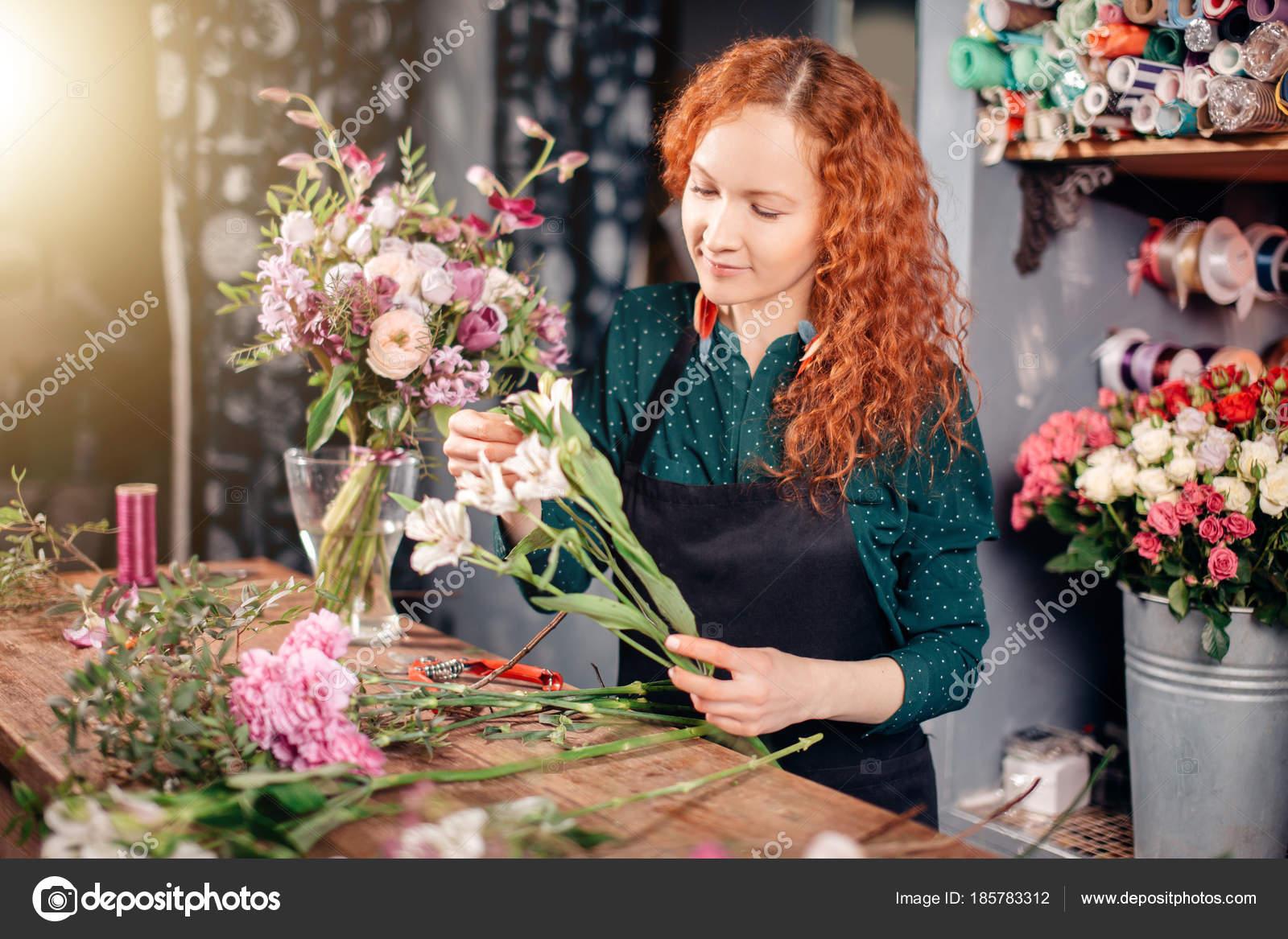 Портрет молода жінка флорист проведення білі квіти і дивлячись на ... 2ed09e0c19d5e