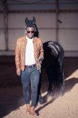 Fotografie afrikanischer Mann mit Sonnenbrille in der Nähe von schwarzes Pferd im hangar