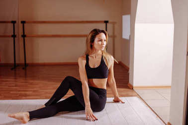Woman stretching seated spinal twist. Young slim girl makes exercise