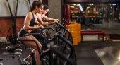 Žena a muž na kole v tělocvičně, cvičení nohy dělat kardio cvičení spinningová kola