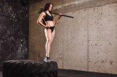 Fotografie Frau mit Hammer im Fitness-Studio. Mädchen mit Vorschlaghammer in der Ausbildung