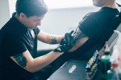 Fotografia Rende maestro tatuatore in guanti tatuaggio