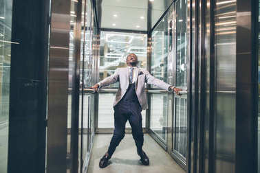 african Businessman screaming in elevator. fear claustrophobia concept